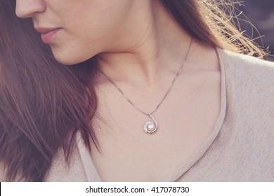 Detal of woman wearing a luxury pearl pendant