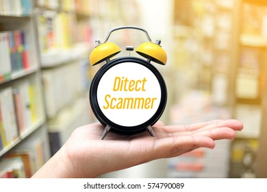 Detect Scammer  - business concept hand holding clock on blurred bookstore as background