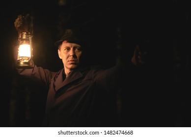 Detective agent with gun and kerosene lamp in night park.