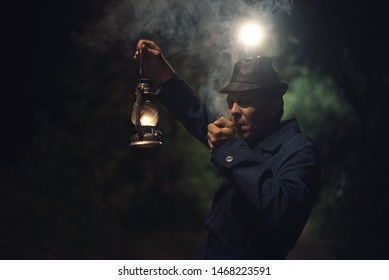 Detective agent in a hat and coat is holding in hand a kerosene lamp and smokes his smoking pipe.