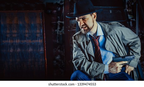 Detective with the gun wearing a fedora hat and a trench coat, dark background.