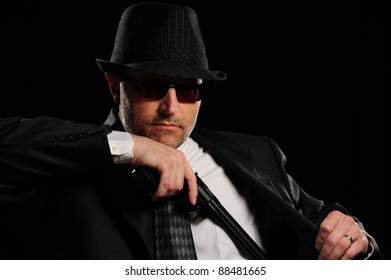 Detective gunman pulling a large gun from his business suit.