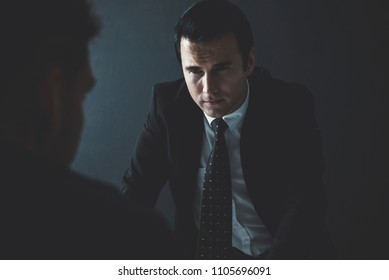 Detective interviewing suspect or criminal man in interrogation room