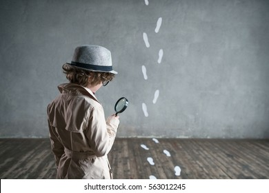 Detective with a magnifying glass in studio