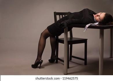 Detective scene imitation. Woman in a black suit lying on a table