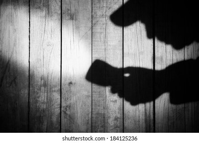 Detective Silhouette with a searchlight on Grungy Wooden Background.