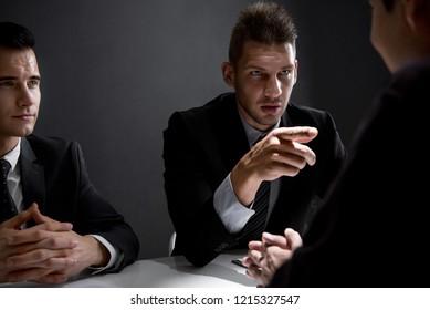 Detectives interview suspect or criminal man in interrogation room