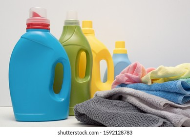 Detergent bottles and dirty linen on white background. Laundry concept.