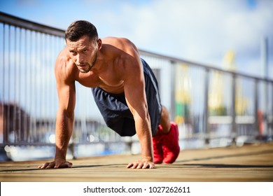 Determinated and athletic man doing pushups shirtless during workout session in the city