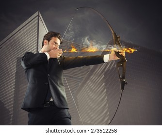 Determinated businessman with flaming arrow takes aim