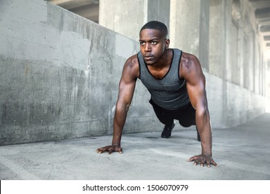 Determined african american male athlete training in city, on concrete surface in morning, workout