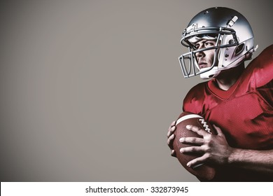 Determined American football player looking away while holding ball against grey background with vignette