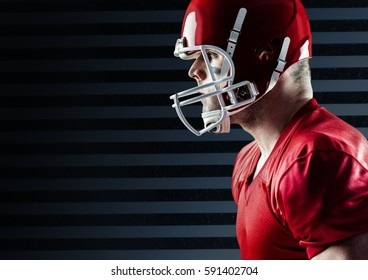 Determined american football player standing against striped black background