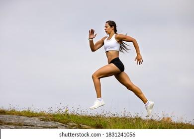 Determined Athlete Running On Mountain Against Sky