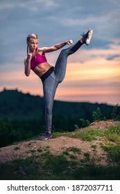Entschlossene Sportlerin, die bei Sonnenuntergang, gemischten Kampfkünsten, MMA, Tae-Bo-Position einen hohen Kick macht