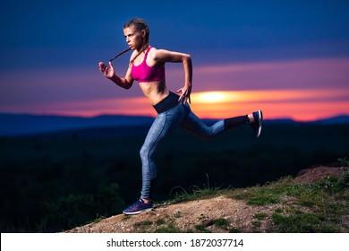Entschlossene Sportlerin, die bei Sonnenuntergang auf Hügeln läuft