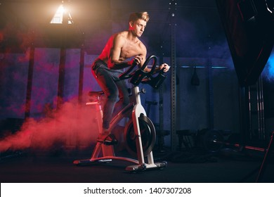 Determined bare-chested sportsman engaged in a bicycle simulator in the gym, warming up before powerlifting workout