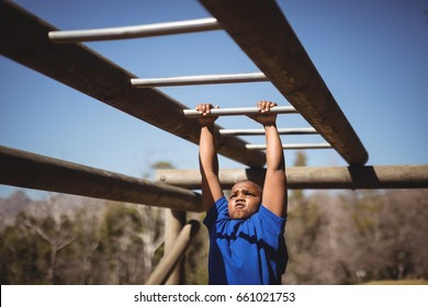 Determined boy exercising on monkey bar during obstacle course in boot camp