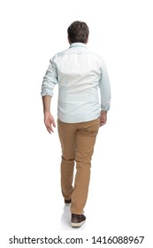 Determined casual man walking forward hurried while wearing a white shirt on white studio background
