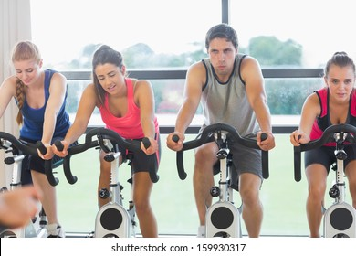 Determined four people working out a class in gym