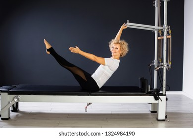 determined and happy woman practicing  on Pilates reformer