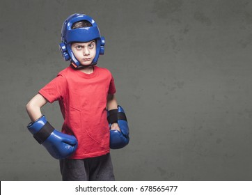 Determined little fighter wearing gloves and helmet. Martial arts kids concept