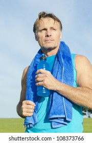 determined looking sportsman holding a blue water bottle with a blue towel around his shoulders.