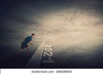 Determined man stands in running position, at the start line, looking ahead confident. Guy sprinter ready for starting 2021 new year challenges. Competitive winner behaviour and motivation concept.