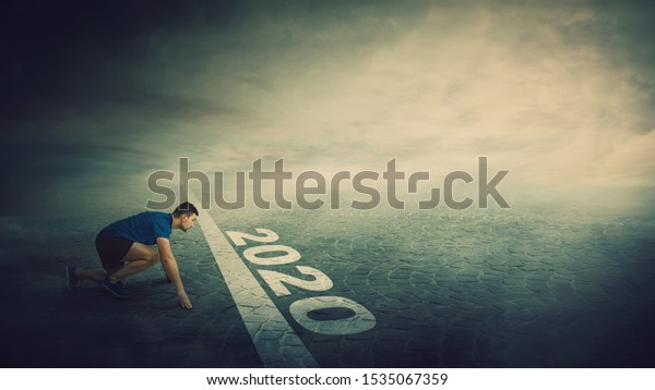 Determined man stands in running position, at the start line, looking ahead confident. Guy sprinter ready for starting 2020 new year challenges. Competitive winner behaviour and motivation concept.