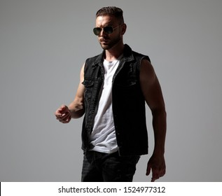 Determined man walking while wearing sunglasses and a black jeans vest on gray studio background