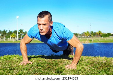 Determined mature man doing pushup exercise on lakeshore
