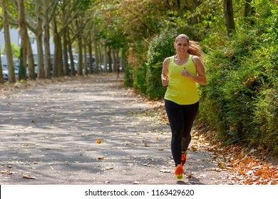 Determined middle-aged woman jogging during cardio workout for burning calories outdoors in the park in Autumn