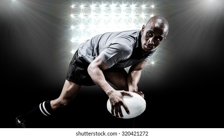 Determined sportsman looking away while playing rugby against spotlight