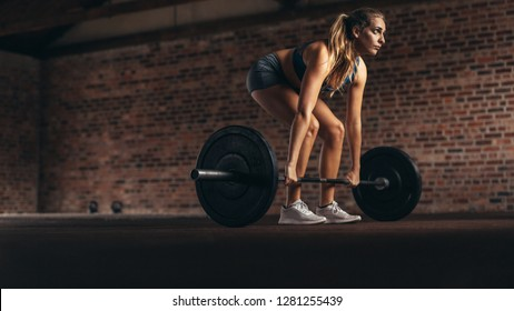 Determined and strong fitness woman training with heavy weights in fitness club. Female athlete doing weight lifting exercise in gym.