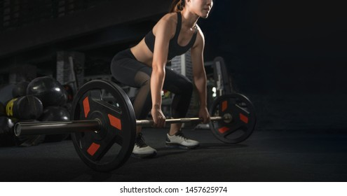 Determined and strong fitness woman training with heavy weights in fitness club. Female athlete holding heavy weight barbell in gym. Woman weightlifter preparing for training. Training with barbell