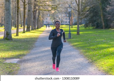 Determined  strong young African woman training in a park jogging along a tree-lined avenue in a park