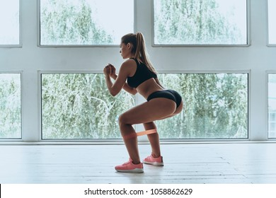 Determined to win. Modern young woman in sport clothing crouching using resistance band while exercising in the gym
