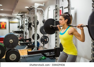 Determined woman lifting a barbell at the gym