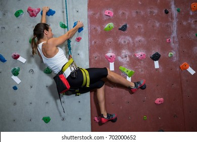 Determined woman practicing rock climbing in fitness studio