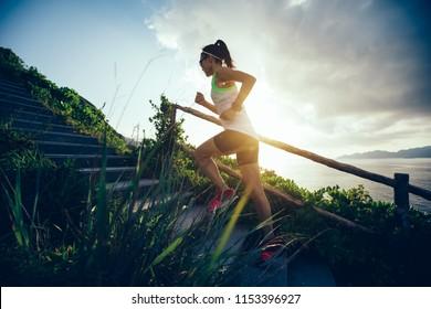Entschlossene Frau, die auf einer Bergtreppe am Meer hochläuft