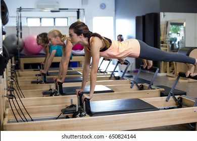 Determined women practicing stretching exercise on reformer in gym