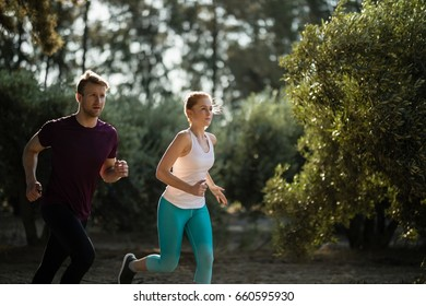 Determined young couple running on field at farm during sunny day