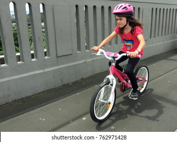 Determined young girl (age 07) rides a bike on a city street. Real people. Copy space