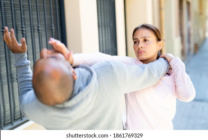 Determined young Latina using Krav Maga techniques to protect herself from attacker man on city street. Female self-defense concept..