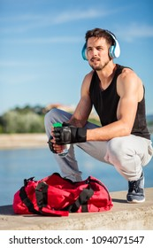 Determined young man pulling water bottle out of his gym bag before the workout. Urban exercise on the riverbank