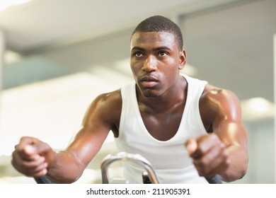 Determined young man working out on exercise bike at the gym