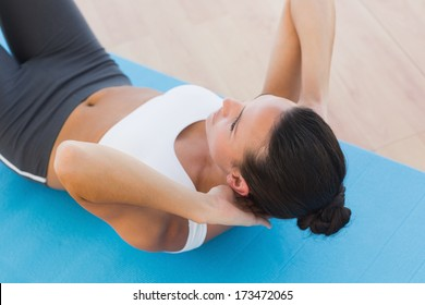 Determined young woman doing abdominal crunches on exercise mat at a gym