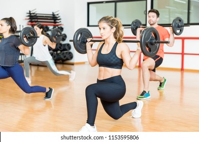 Determined young woman doing barbell lunges with friends in health club