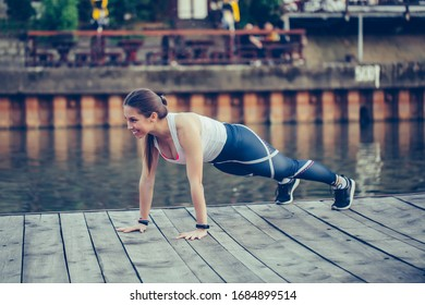 Determined young woman doing push up in nature, by the river.