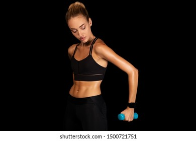 Determined Young Woman Working Out With Dumbbells On Black Studio Background. Strength Exercises. Copy Space